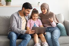 Happy muslim parents teaching daughter using laptop computer, sitting together on sofa at home