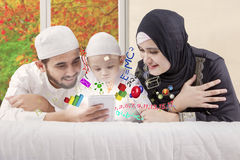 Happy muslim parents teaching math on bed Royalty Free Stock Photography