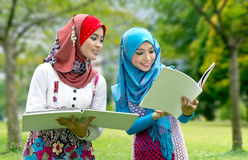 Happy muslim students. Two happy young female muslim students with open folders in summery park Royalty Free Stock Photo