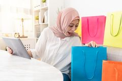 Happy muslim woman using mobile digital tablet pad stock photography