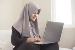 Happy Muslim Woman Working with Laptop in Her Bedroom. Portrait of happy smiling Asian muslim woman working with laptop in her bedroom, casual modern lifestyle stock photo