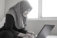 Happy Muslim Woman Working with Laptop in Her Bedroom. Portrait of happy smiling Asian muslim woman working with laptop in her bedroom, casual modern lifestyle stock photography