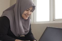 Happy Muslim Woman Working with Laptop in Her Bedroom. Portrait of happy smiling Asian muslim woman working with laptop in her bedroom, casual modern lifestyle royalty free stock photo
