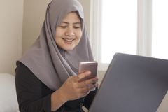 Happy Muslim Woman Working with Laptop and Smart Phone in Her Bedroom stock images