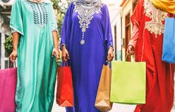 Happy Muslim women doing shopping in the city center - Arabian teen girls having fun buying new traditional Arab clothes in mall stock image