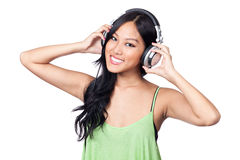 Happy with my music. A young Asian girl looking happy while listening to music through DJ style headphones Stock Photography