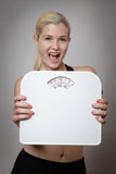 Happy with my weight. Happy fitness woman holding scales Royalty Free Stock Photo