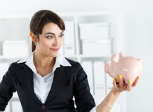 Happy and mysterious beautiful woman holding funny piggybank in Stock Photo
