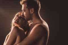 Happy naked lovers hugging and looking at each other,. On brown stock photo