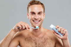 Happy naked young man cleaning teeth with toothbrush and toothpaste. Over grey background Royalty Free Stock Photos