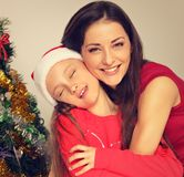 Happy natural smiling mother embrace her cute daughter with enjoying closed eyes in santa clause hat on Christmas green fur tree stock photography