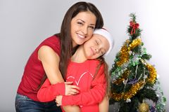 Happy natural smiling mother embrace her cute daughter in santa clause hat on Christmas green fur tree royalty free stock image