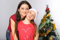 Happy natural smiling mother embrace her cute daughter in santa clause hat on Christmas green fur tree studio background. Closeup stock photos