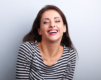 Happy natural toothy laughing casual woman with wide open mouth. And closed eyes on blue background Stock Image
