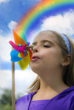 Happy in nature. A child - girl blowing to her colorful pinwheel and rainbow like a concept for happy future, happy mood and Stock Photo