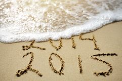 Happy Near Year concept 2015 replace 2014 on sea beach Royalty Free Stock Photo