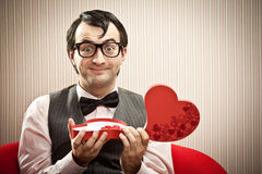 Happy nerd man open chocolate box love gift.  Stock Images