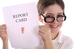 Happy nerd with report card glasses down. Shot of a Happy nerd with report card glasses down Royalty Free Stock Photography