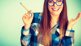 Happy nerdy woman in glasses holding pen Stock Photography
