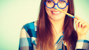 Happy nerdy woman in glasses holding pen Royalty Free Stock Photos