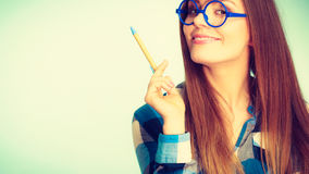 Happy nerdy woman in glasses holding pen Royalty Free Stock Image