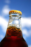 Happy New Beer. Focus On The Neck Of A Full Unopened Bottle Of Beer In Front Of A Blue Cloudy Sky Royalty Free Stock Image
