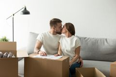 Happy new home owners kissing on sofa moving in house. Happy couple kissing on sofa moving in own house, young men and women sitting on couch with cardboard Royalty Free Stock Photo