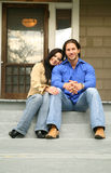 Happy With New House. Two people sit in front of their new house with happy expression royalty free stock image