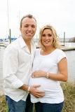 Happy new parents. Young happy Caucasian couple outside at a marina, maternity portraits Stock Images