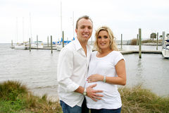 Happy new parents. Young happy Caucasian couple outside at a marina, maternity portraits Stock Photography