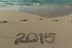 Happy-new-wave-1. Foamy wave washes a sign of new year written on a sandy shore Stock Images