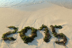 Happy-new-wave-3. Foamy wave washes a sign of new year written on a sandy shore Royalty Free Stock Images