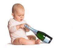 Happy New Year. Baby tries to open a bottle of champagne. A good photo for congratulations or celebrations or to symbolize success royalty free stock image