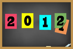 Happy new year 2012. New year 2012 sticker pasted on the blackboard Stock Images