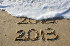 Happy New Year 2013. 2013 written in the sand with 2012 washed away by the surf stock image