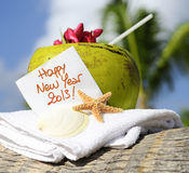 Happy new year 2013. Coconut cocktail starfish tropical Caribbean beach refreshment and towel Royalty Free Stock Photo