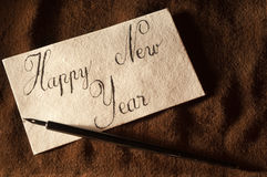 Happy New Year. Close-up of a handwritten greeting card and dip pen Stock Images