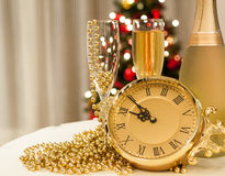Happy new year. New year celebration setting with two glasses and bottle of champagne, clock and christmas tree lights in the background stock images