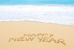 Happy New Year from Africa. Happy New Year written on sand of an exotic beach Stock Photos