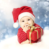 Happy New Year baby with red gift on snow. Background royalty free stock image