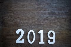 Cut wood number 2019 on old wooden table from top view with space. royalty free stock image