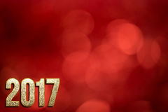 Happy New Year 2017. Background with gold sparkling texture font and red bokeh background for dust for flyer, poster, for holiday design, banner. calendar
