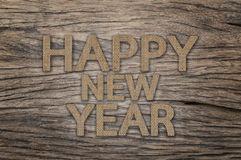 Happy New Year background. Happy New Year, Text design from sackcloth on wood background Stock Photo