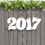 Happy New Year background on wood. Happy New Year background with hanging numbers on a snowy wood background Royalty Free Stock Images