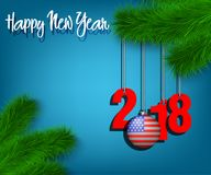 Happy New Year 2018 and ball with the USA flag. Happy New Year numbers 2018 and christmas ball painted in the colors of the USA flag hanging on a Christmas tree Royalty Free Stock Image