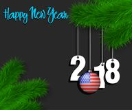 Happy New Year 2018 and ball with the USA flag. Happy New Year numbers 2018 and christmas ball painted in the colors of the USA flag hanging on a Christmas tree Stock Images