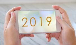 2019, happy new year banner on smart phone device screen background, new year greeting card banner, communication and technology. Concept stock photography