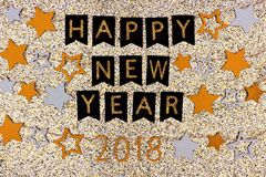 Happy New Year 2018 text banner with strings of stars against glittery gold Stock Photos