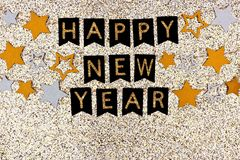 Happy New Year banner with strings of stars against glittery gold. Happy New Year banner with strings of gold and silver stars against a glittery gold background Royalty Free Stock Images