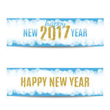 Happy New Year 2017 banners golden text and snowflakes. Happy New Year 2017 banners set. Blue background with bokeh, snow, fog and snowflakes. Golden text Stock Image